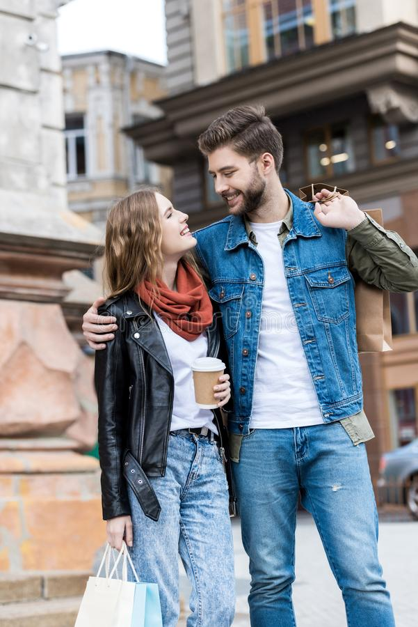 ritratto delle coppie sorridenti con stare dei sacchetti della spesa immagine stock