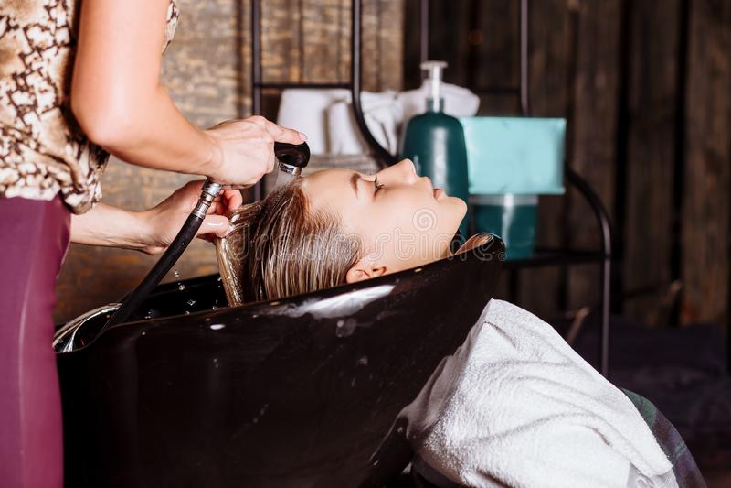 Ritratto delle donne che lavano i capelli in un salone di bellezza fotografie stock