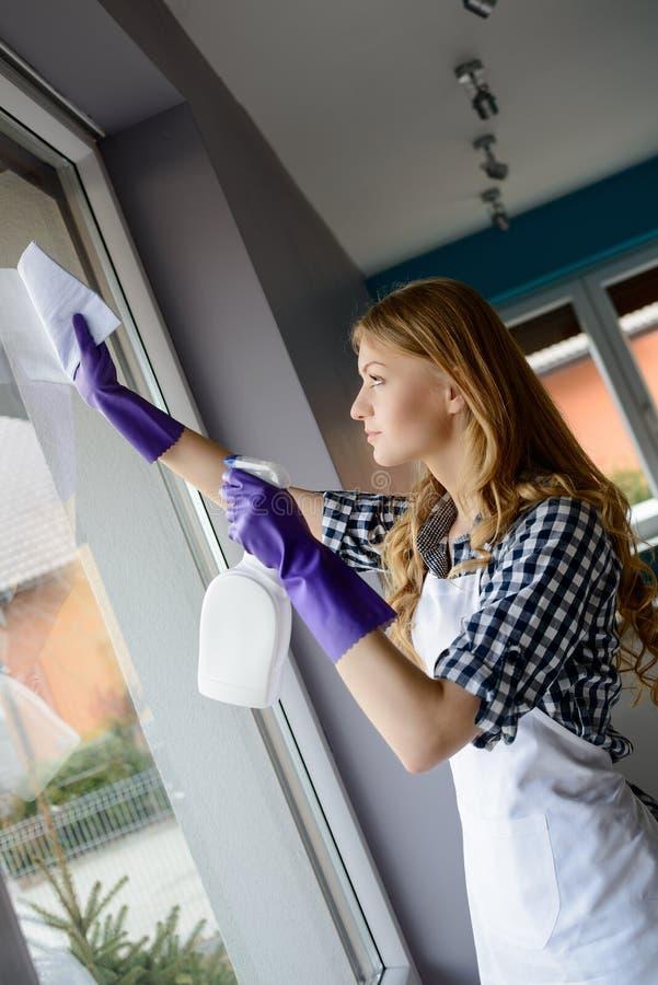 Ritratto delle finestre attraenti di pulizia della giovane donna fotografie stock libere da diritti