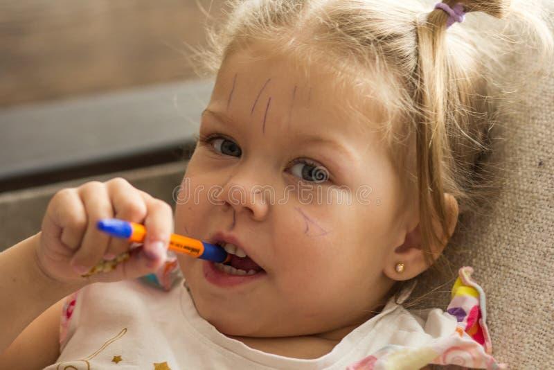 Ritratto delle linee di disegno di una bambina sul suo fronte fatto dalla penna fotografia stock libera da diritti