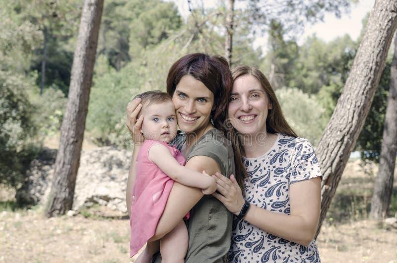 Ritratto delle madri felici delle lesbiche con un bambino Fami omosessuale fotografia stock