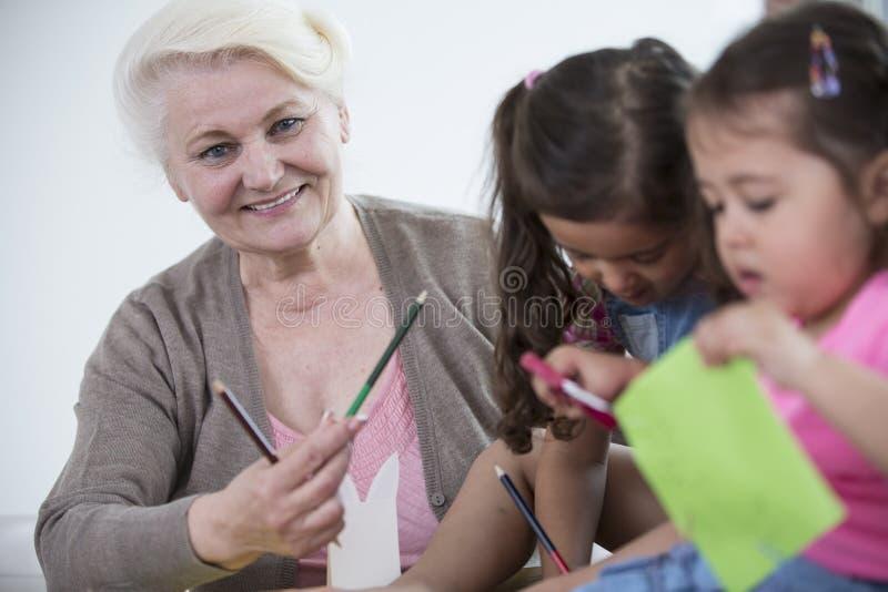 Ritratto delle nipoti d'aiuto della donna senior nella fabbricazione degli artigianato a casa immagine stock
