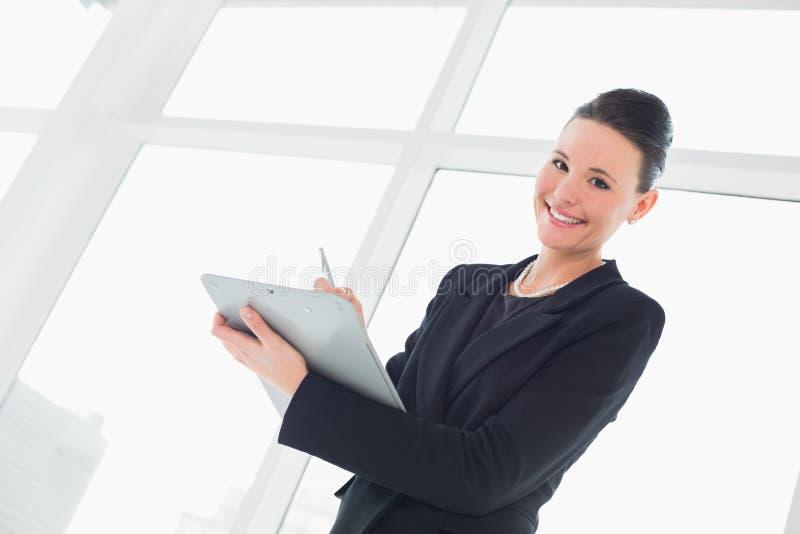 Ritratto delle note eleganti sorridenti di una scrittura della donna di affari fotografia stock