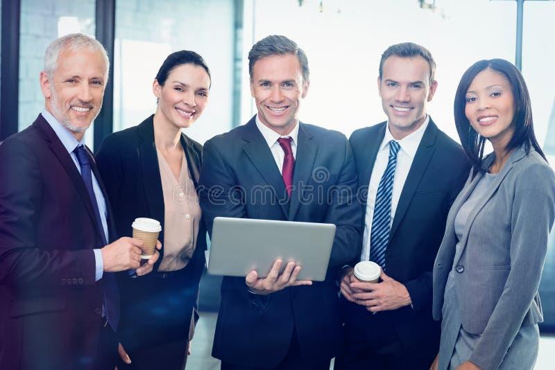 Ritratto delle persone di affari che stanno insieme al computer portatile fotografia stock