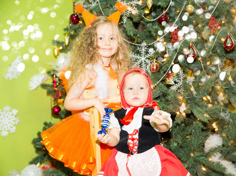 Ritratto delle ragazze dei bambini negli scoiattoli di un vestito intorno ad un albero di Natale decorato Bambini sul nuovo anno  immagini stock