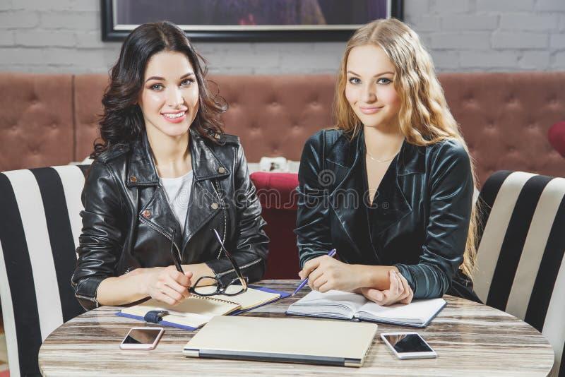 Ritratto delle ragazze sorridenti che si siedono alla tavola Riunione d'affari teamwork fotografia stock libera da diritti