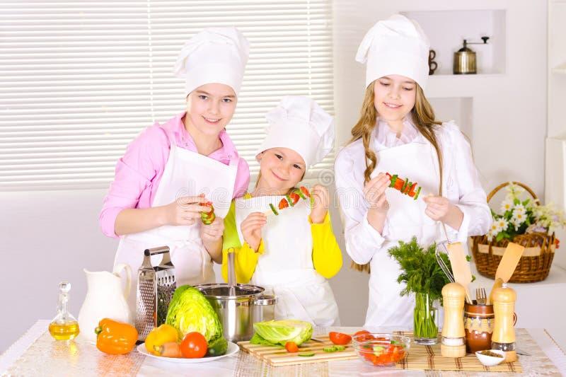 Ritratto delle ragazze sveglie felici che cucinano legumiera fotografia stock libera da diritti