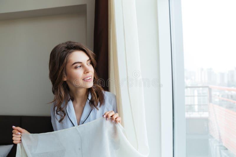 Ritratto delle tende della donna di finestra felici di apertura fotografie stock libere da diritti