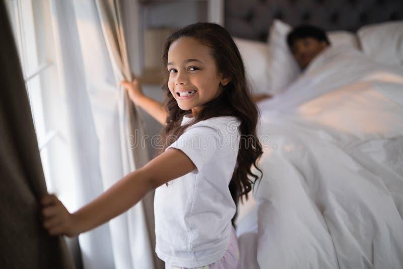Ritratto delle tende felici della tenuta della ragazza in camera da letto immagine stock libera da diritti