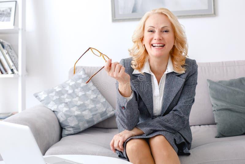 Ritratto dello psicologo della donna che si siede alla risata casuale del Ministero degli Interni allegra immagini stock