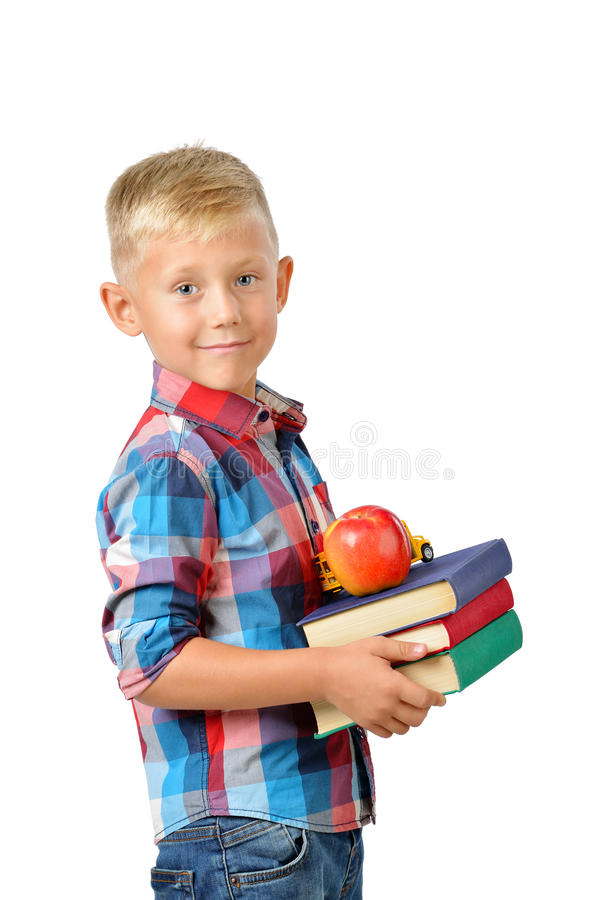 Ritratto dello scolaro felice con i libri e della mela isolata su fondo bianco Istruzione fotografia stock libera da diritti