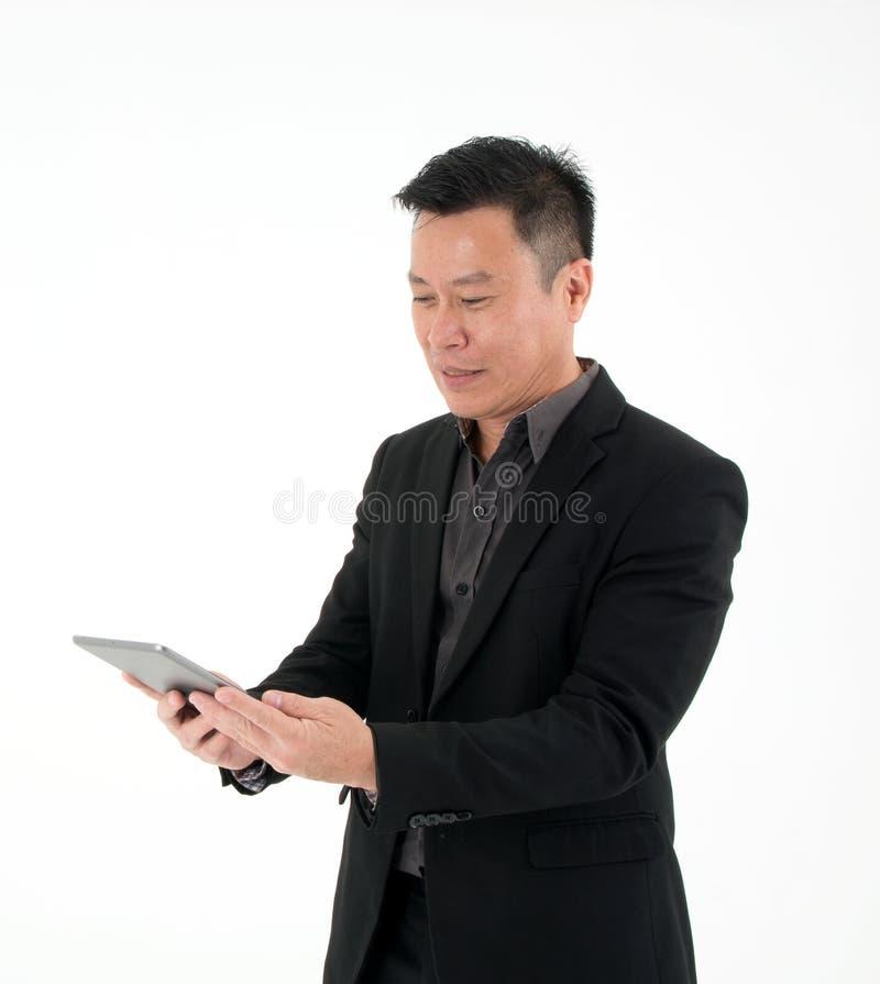 Ritratto dello sguardo dell'uomo d'affari alla compressa per cercare informazioni isolato su fondo bianco fotografia stock