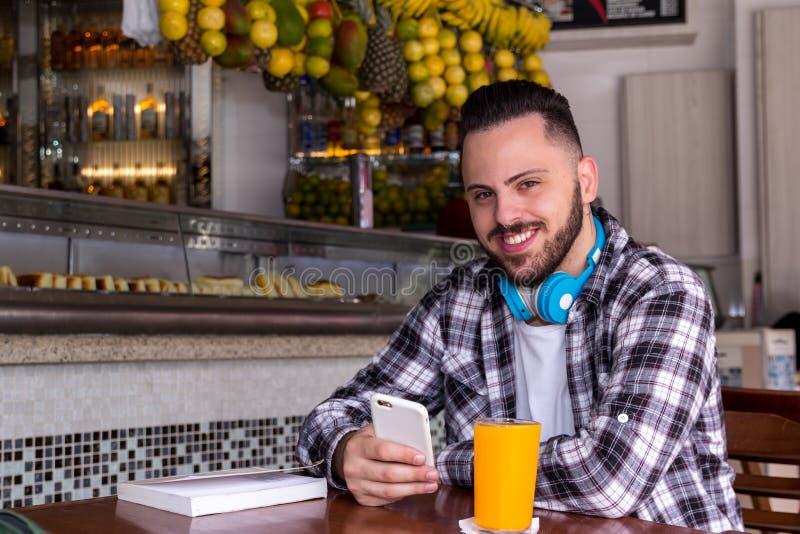Ritratto dello smartphone della tenuta del tipo del consumatore fuori dello snack bar brasiliano immagini stock