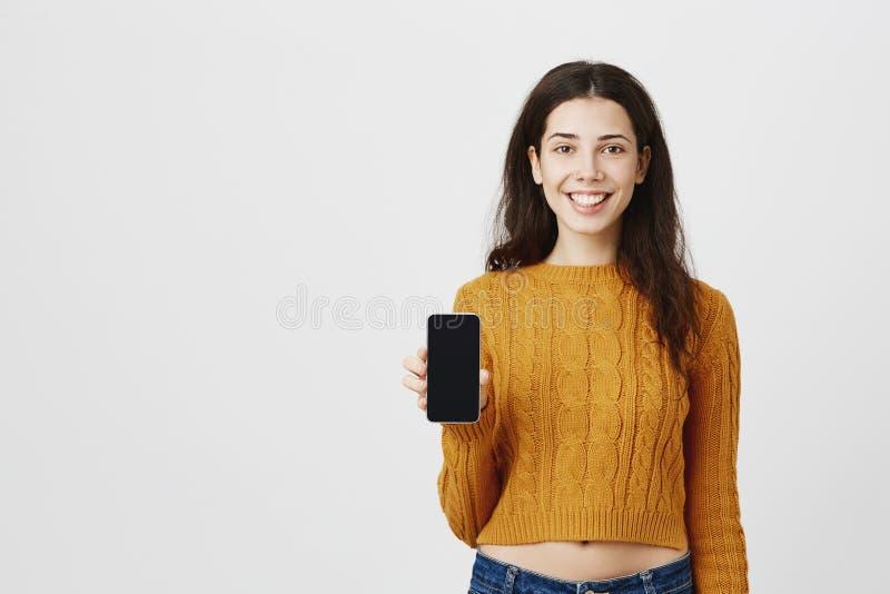 Ritratto dello smartphone sorridente attraente sveglio di pubblicità della donna, aggeggio della tenuta a disposizione per mostra fotografia stock libera da diritti