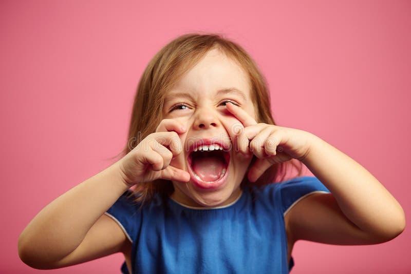 Ritratto dello smorfia della bambina sul rosa isolato immagine stock