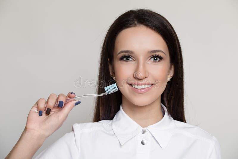 Ritratto dello spazzolino da denti sorridente della tenuta della donna del dentista a disposizione fotografia stock