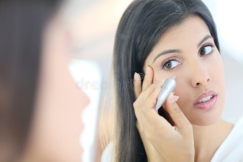 Ritratto dello specchio della giovane donna che applica correttore fotografia stock