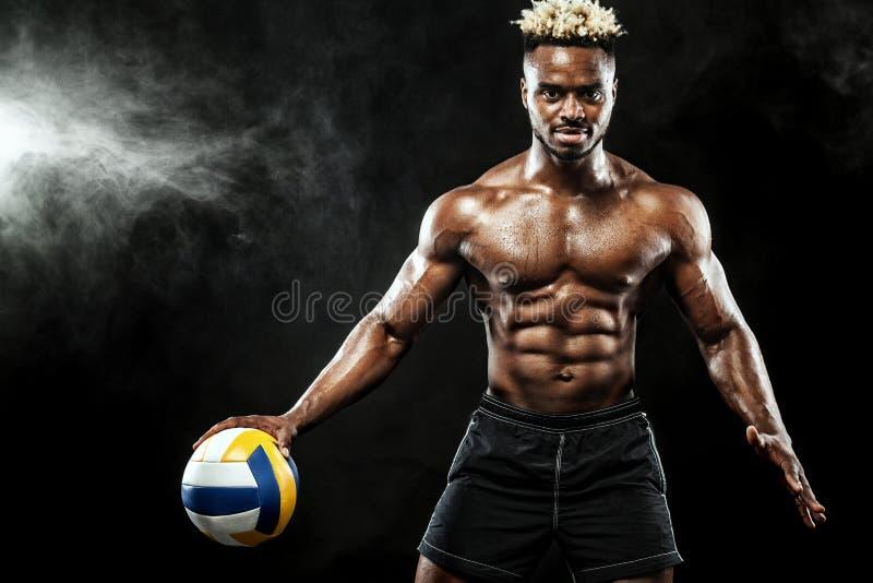 Ritratto dello sportivo afroamericano, giocatore del valleyball con una palla sopra fondo nero Giovane adatto in abiti sportivi immagini stock libere da diritti