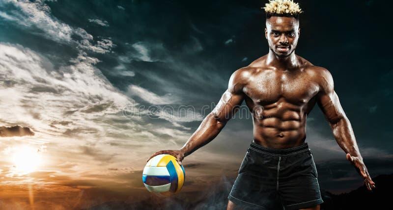 Ritratto dello sportivo afroamericano, giocatore di beach volley con una palla sopra il fondo del cielo Giovane adatto dentro fotografie stock libere da diritti