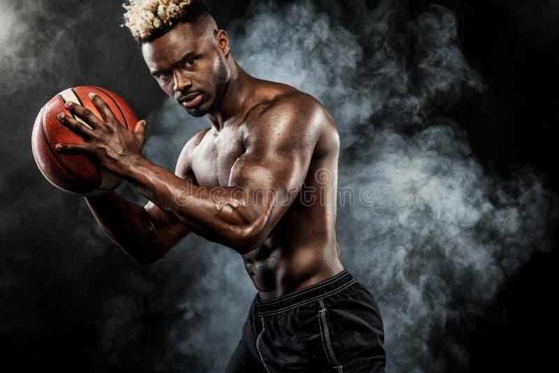 Ritratto dello sportivo afroamericano, giocatore di pallacanestro con una palla sopra fondo nero Giovane adatto in abiti sportivi fotografie stock libere da diritti