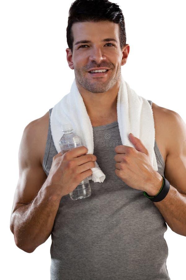 Ritratto dello sportivo stanco sorridente con l'asciugamano e la bottiglia fotografia stock
