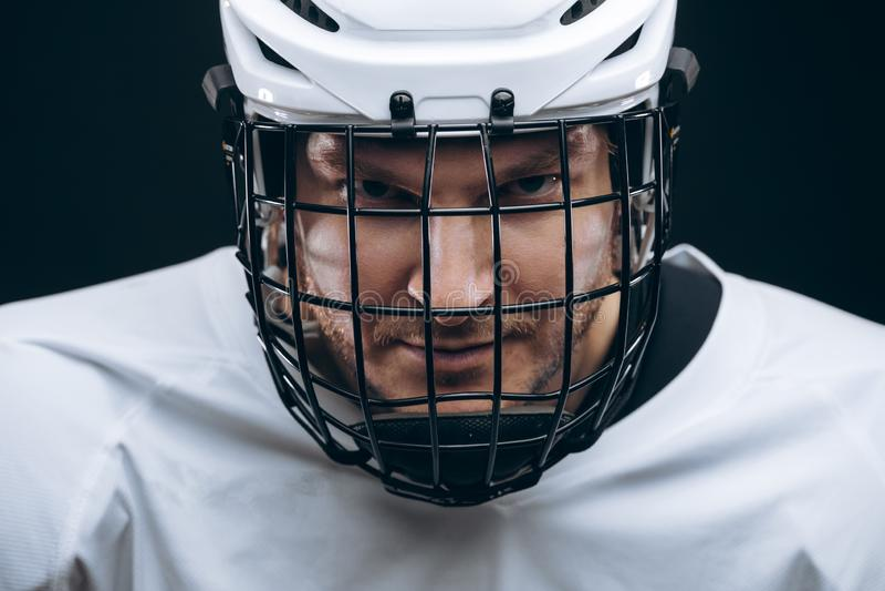 Ritratto dello sportivo in uniforme dell'hockey sopra fondo nero immagini stock