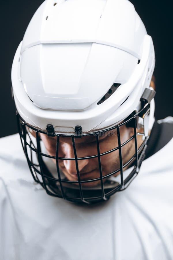 Ritratto dello sportivo in uniforme dell'hockey sopra fondo nero fotografia stock libera da diritti