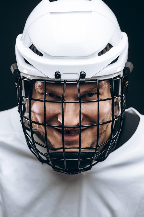 Ritratto dello sportivo in uniforme dell'hockey sopra fondo nero immagine stock