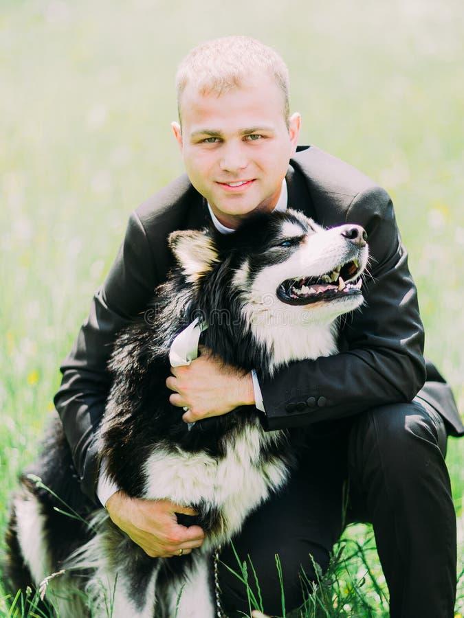 Ritratto dello sposo sorridente che abbraccia il cane sveglio nel campo fotografia stock