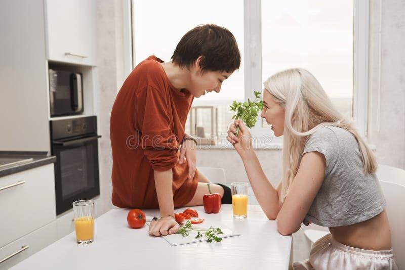 Ritratto dello stipendio biondo sveglio e di conversazione della tenuta della ragazza con sua amica mentre si siede sul tavolo da fotografia stock