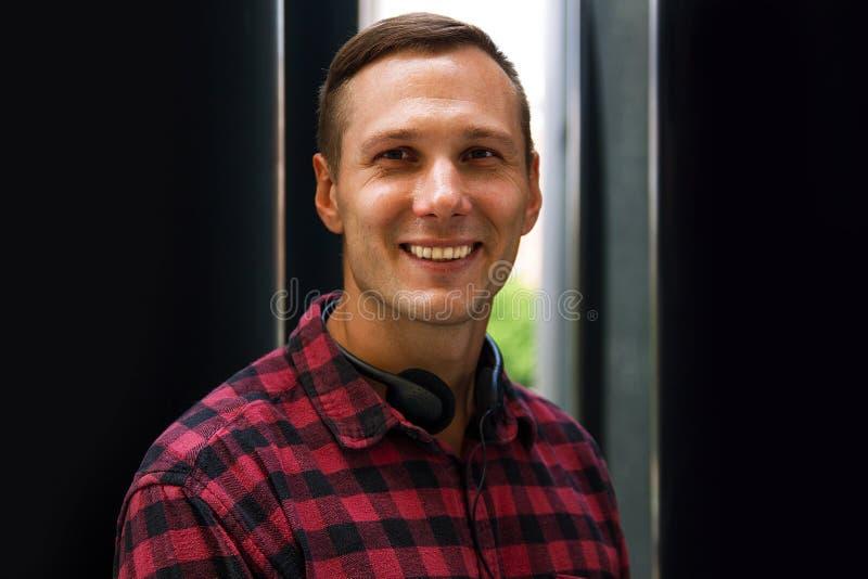 Ritratto dello studente del giovane alla stazione ferroviaria con sorridere delle cuffie immagini stock