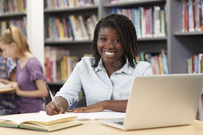 Ritratto dello studente femminile Working At Laptop della High School in Libr fotografie stock libere da diritti