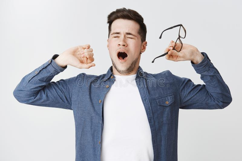 Ritratto dello studente maschio attraente stanco che decolla i vetri che chiudono gli occhi e che sbadigliano mentre allungando c fotografia stock