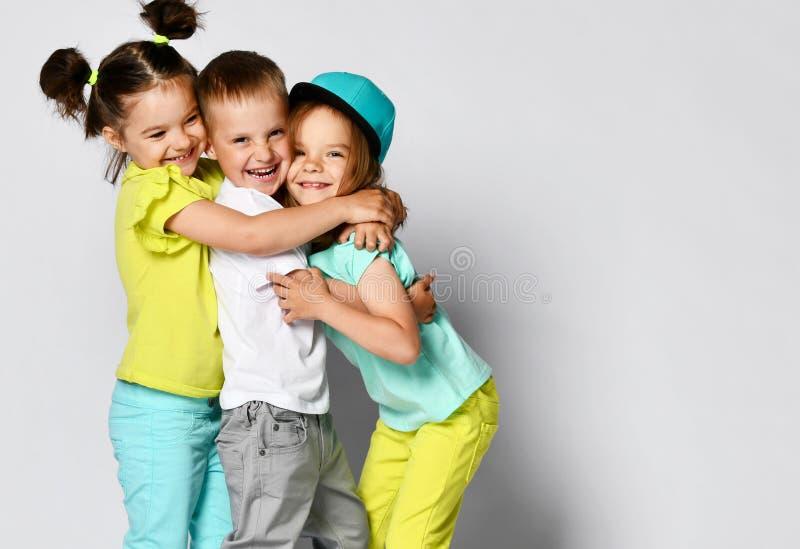 Ritratto dello studio dei bambini su un fondo leggero: un colpo pieno del corpo di tre bambini in vestiti luminosi, due ragazze e immagine stock