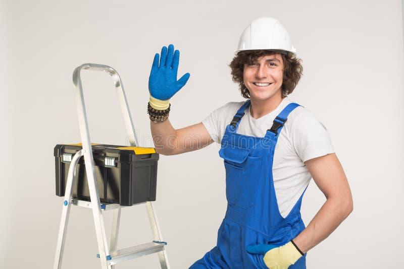 Ritratto dello studio del costruttore bello in casco bianco e camice blu che stringe la sue mano e risata immagine stock libera da diritti