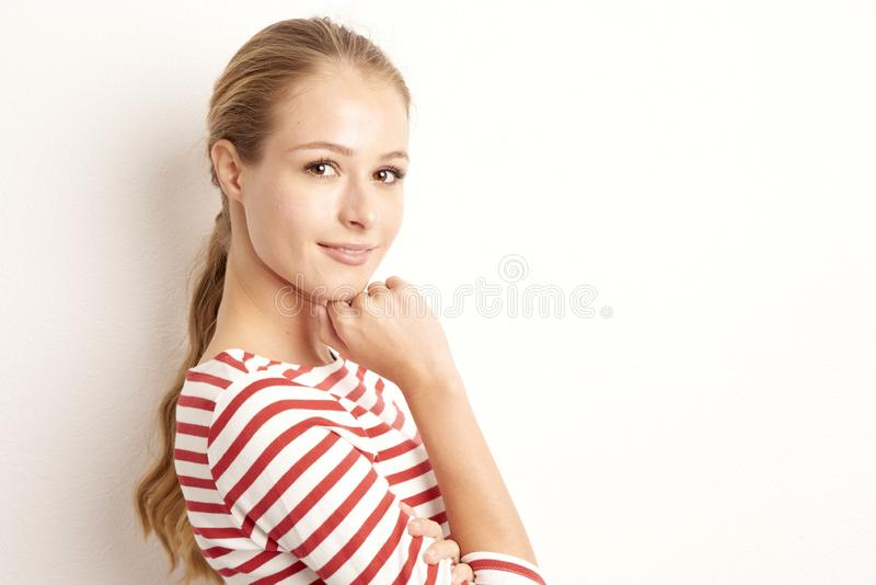 Ritratto dello studio del lookig grazioso della giovane donna alla macchina fotografica ed a sorridere mentre stando al fondo bia immagini stock libere da diritti