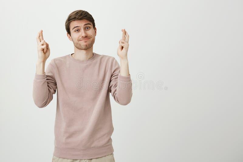 Ritratto dello studio del modello maschio affascinante divertente che sta con il sorriso ansioso e le dita attraversate, sperante fotografie stock libere da diritti