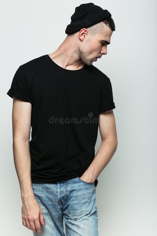 Ritratto dello studio del tipo che posa contro il fondo grigio fotografia stock