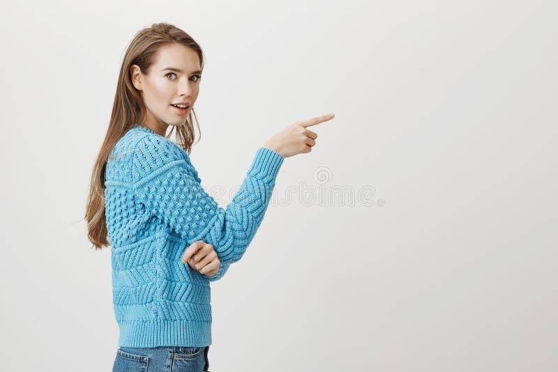 Ritratto dello studio della donna caucasica sorpresa e stupita che sta nel profilo e che indica destra, girantesi verso la macchi immagine stock libera da diritti