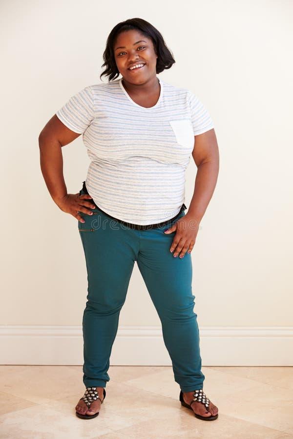 Ritratto dello studio della donna di peso eccessivo sorridente fotografia stock