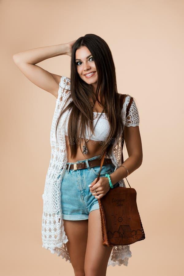 Ritratto dello studio della ragazza alla moda ed attraente emozionale che posa, sorridente ed esaminante macchina fotografica Sta immagini stock