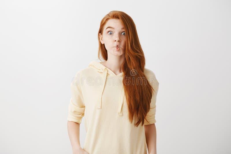 Ritratto dello studio delle labbra pieganti della donna divertente emotiva della testarossa come il pesce, facendo gli occhi schi fotografia stock