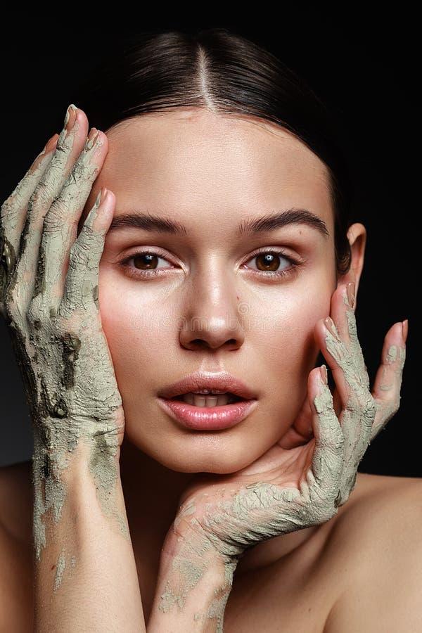 Ritratto dello studio di bella donna con la maschera della mano del fango sulla b nera immagine stock