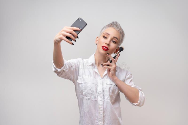 Ritratto dello studio di bella ragazza d'avanguardia con i capelli di scarsità e comporre rimandare braccio sulla vita e presa de immagini stock