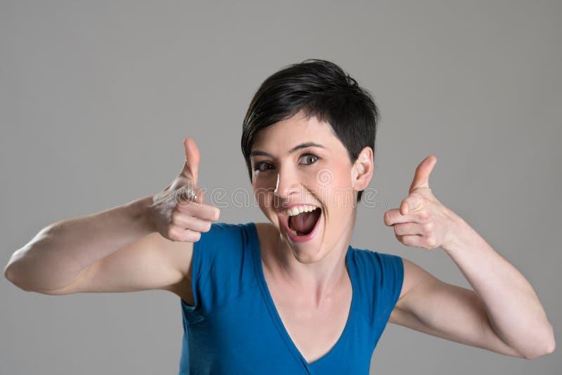 Ritratto dello studio di bellezza castana energetica emozionante che indica dito verso la macchina fotografica immagini stock