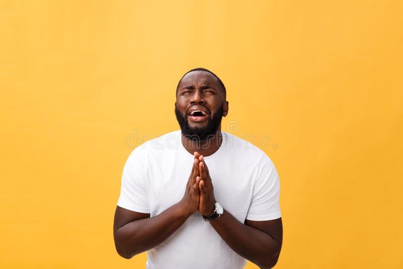 Ritratto dello studio di giovane uomo afroamericano in camicia bianca, tenendosi per mano nella preghiera, esaminante la macchina fotografia stock