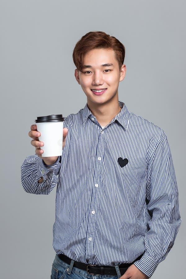 Ritratto dello studio di giovane uomo asiatico orientale che tiene una bevanda sulla tazza di carta fotografia stock libera da diritti