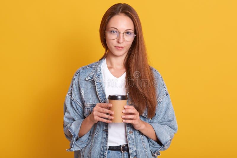 Ritratto dello studio di signora allegra che esamina direttamente la macchina fotografica con piacere, giovane donna che tiene ca fotografia stock