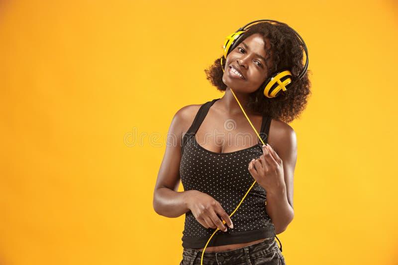 Ritratto dello studio di sorridere felice della ragazza riccia adorabile durante il photoshoot Donna africana sbalorditiva con pe immagine stock