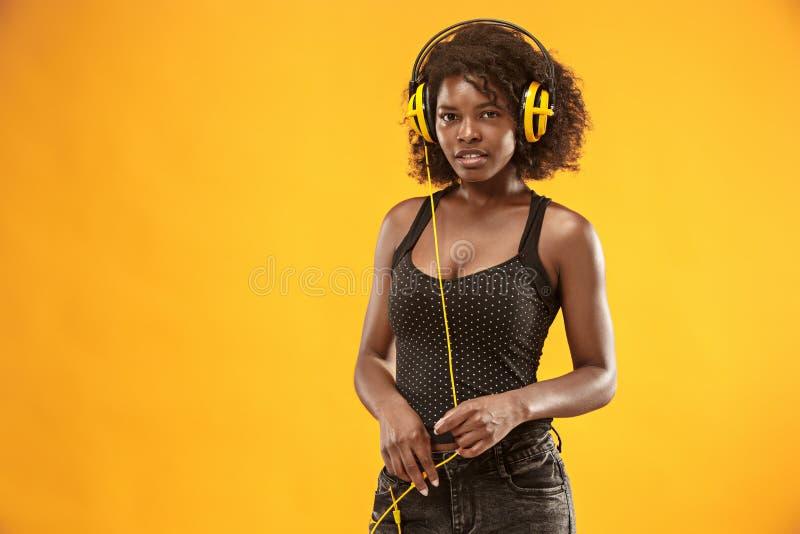 Ritratto dello studio di sorridere felice della ragazza riccia adorabile durante il photoshoot Donna africana sbalorditiva con pe fotografie stock